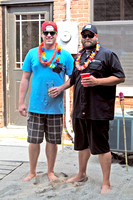"Richard Drawdy, left, and Jason Markkula of the Bank Brewing Co. in Hendricks are pictured barefoot on the ""beach"" they installed out back of the Tap Room especially for the luau."